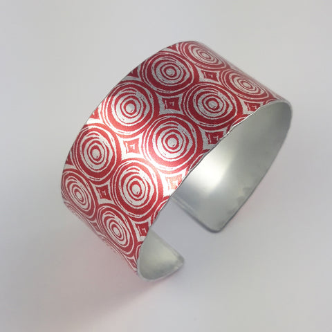 New Dawn Women's Suffrage cuff with a silver and red concentric circles patterns two across with a silvery coloured inside.