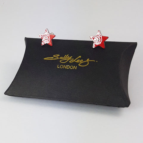 Red aluminium star studs decorated on the side of each one with a silvery linear pattern of abstracted roses. Displayed on a black pillow shaped box with a gold Sally Lees (London) logo.