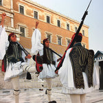 Evzones, Greek Presidential guards, shown in mid-stride with their uniforms.
