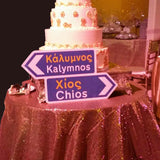A Greek road sign next to a wedding cake.