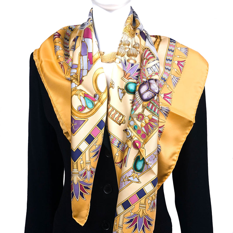 Tresors du Nil Hermes Scarf in Yellows over a black jacket