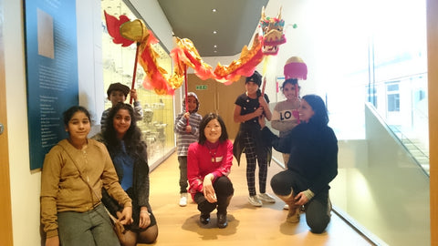 Su Yen pictures with a group of children and Dancing Dragon in the Ashmolean Musuem at Land of Dragon event