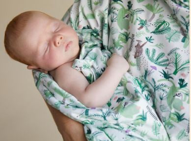 sleeping baby wrapped in an Halcyon Nights wrap with lovely Australian animals on it