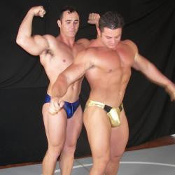 Frank the Tank and Ace Hanson posing a flexing pecs, abs, arms, and thighs
