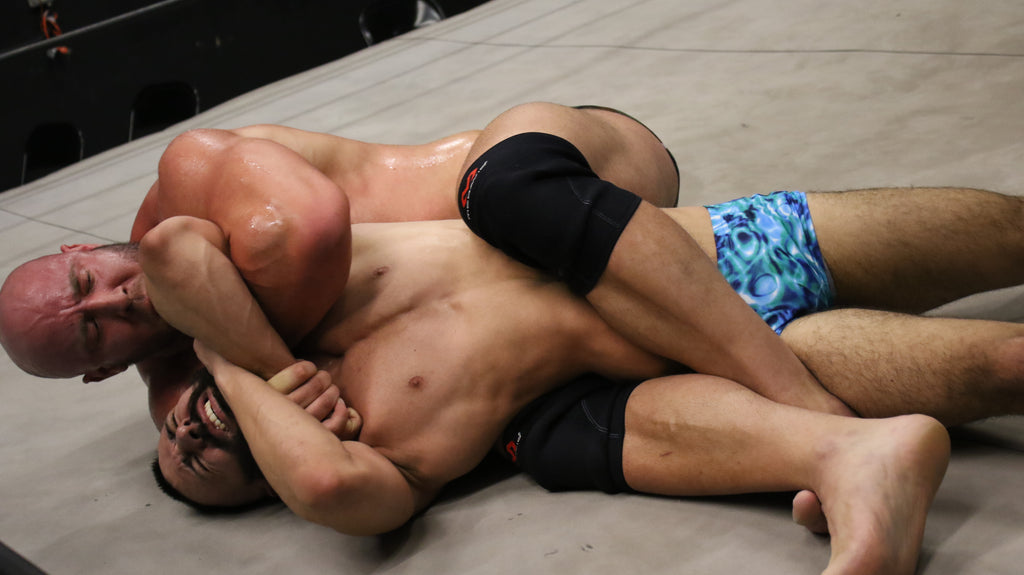 Brute puts Kid Romeo into a head lock and leg scissors at the same time on Thunders Arena.