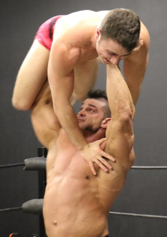 Brian Cage lifts Bolt over his head gorilla press bodybuilder pecs arms