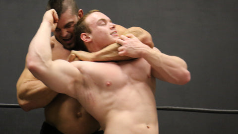 Brian Cage head locks Travis pecs bicep