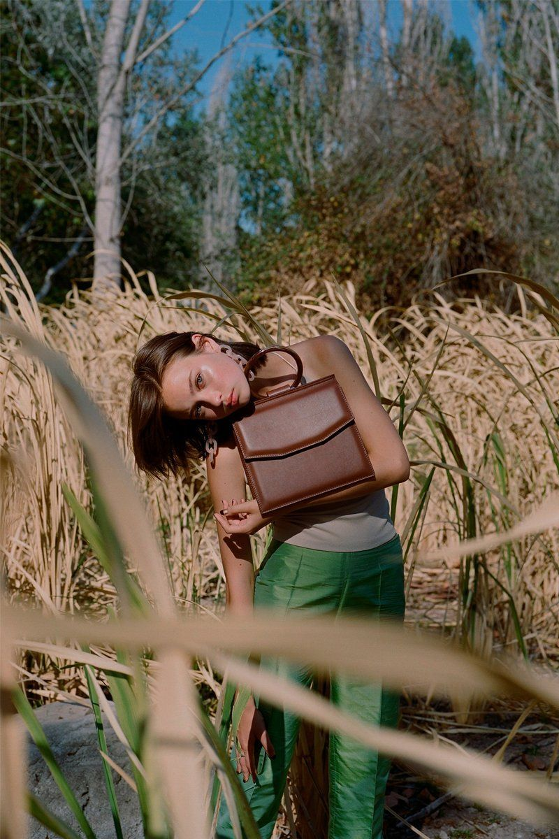 Shellac is dreamy cross body handbag. Limited edition handcrafted with love in Barcelona in spanish calf leather in brown color with a sustainable luxury design. Campaign photo.