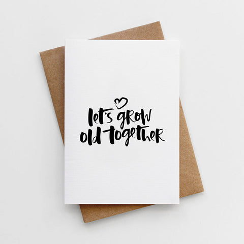 A hand lettered valentines card reading 'Let's Grow Old Together'