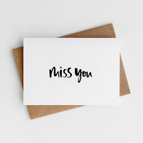 A modern, hand lettered card reading 'Miss You'.