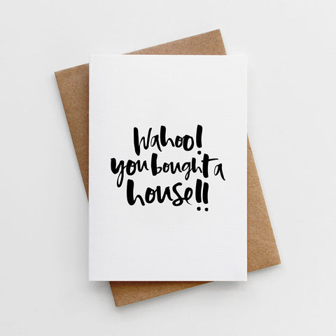A modern hand lettered new home card reading 'Wahoo, You Bought a House!'