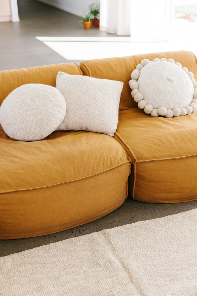 Pampa round white pom pom cushion