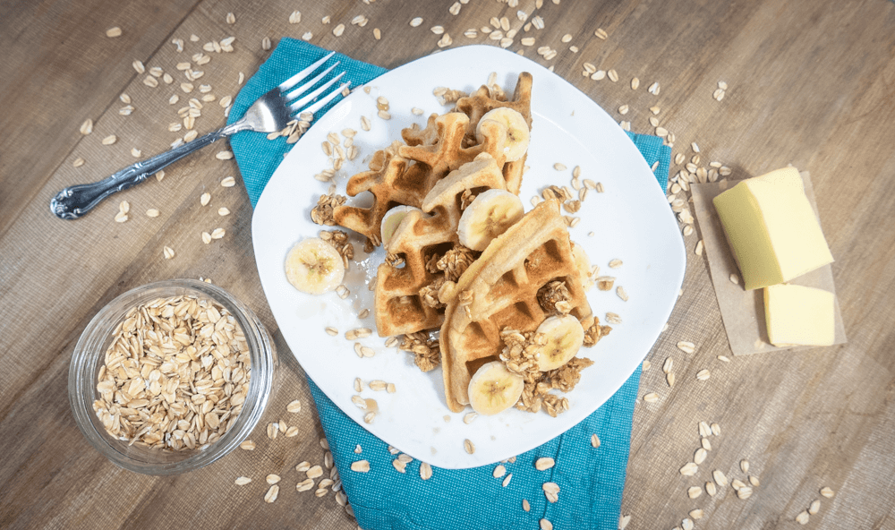 gluten free oat waffles topped with granola and bananas