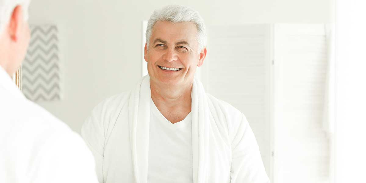 Senior man smiling in front of a mirror in the bathroom