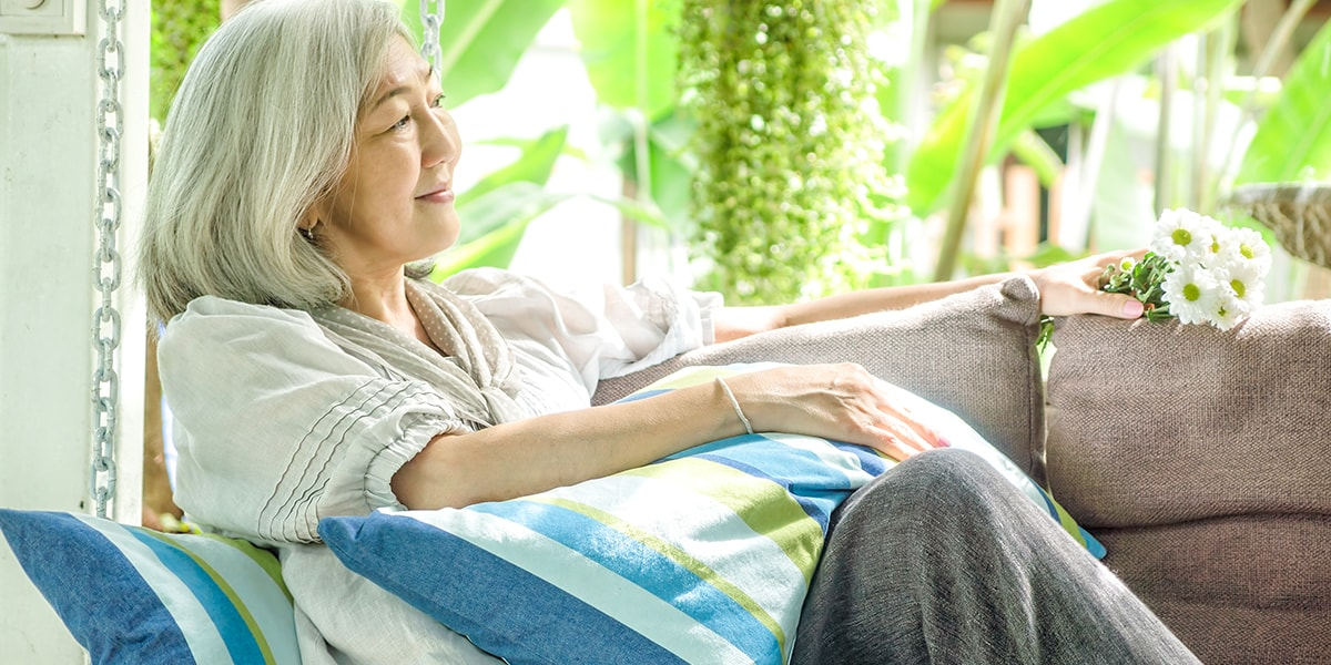 Senior asian woman sitting on couch with colorful pillows inside of refreshing and relaxing room
