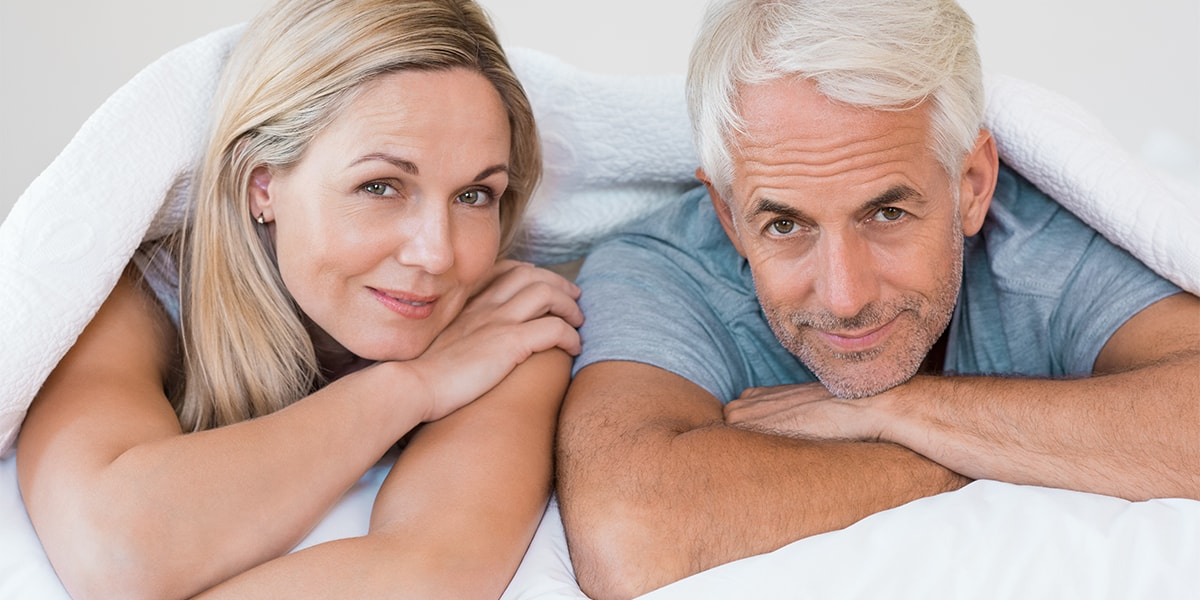 Senior romantic couple under a white duvet in the bed. Happy mature couple lying down in their bed with waterproof Mattress