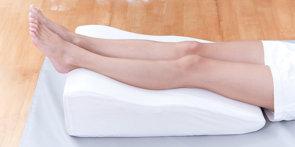A woman's legs lay down on a Leg Elevation Pillow for relaxing and preventing varicose vein