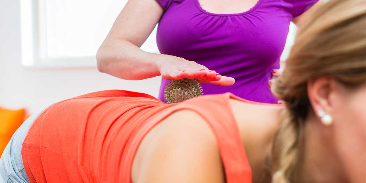 Pregnant young women in sportswear getting backrub with spiky massage ball, focus on massage ball