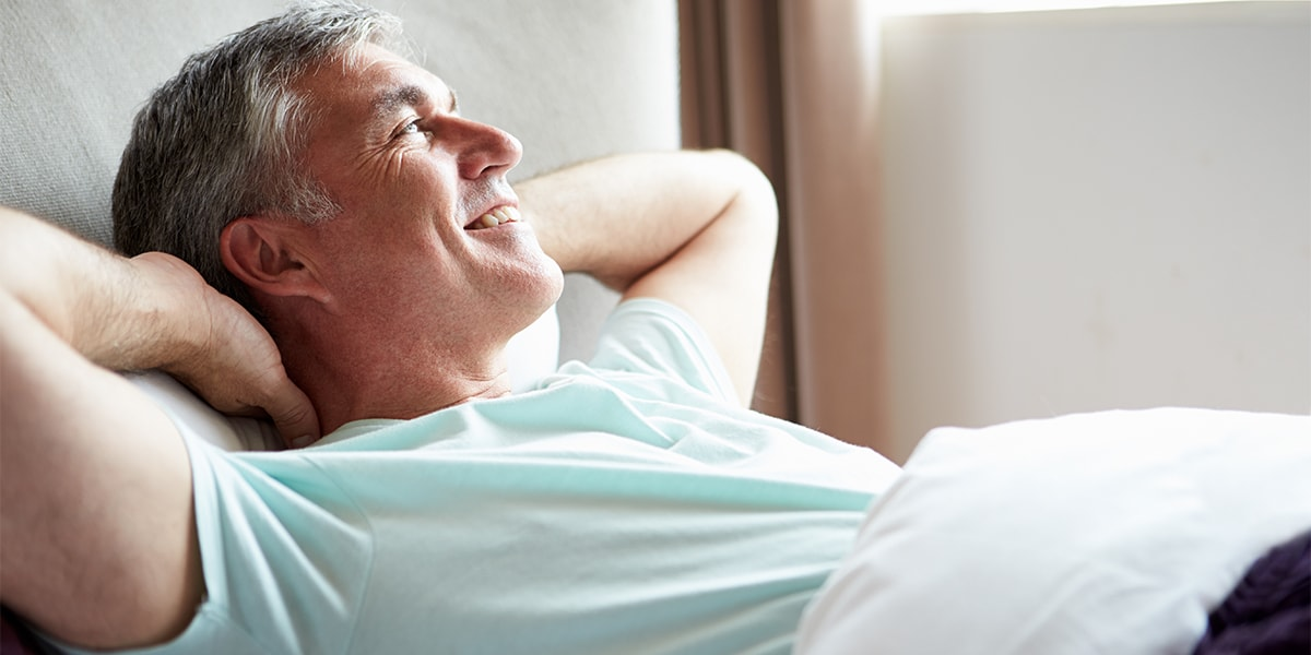 Middle Aged Man lying in bed with wedge pillow