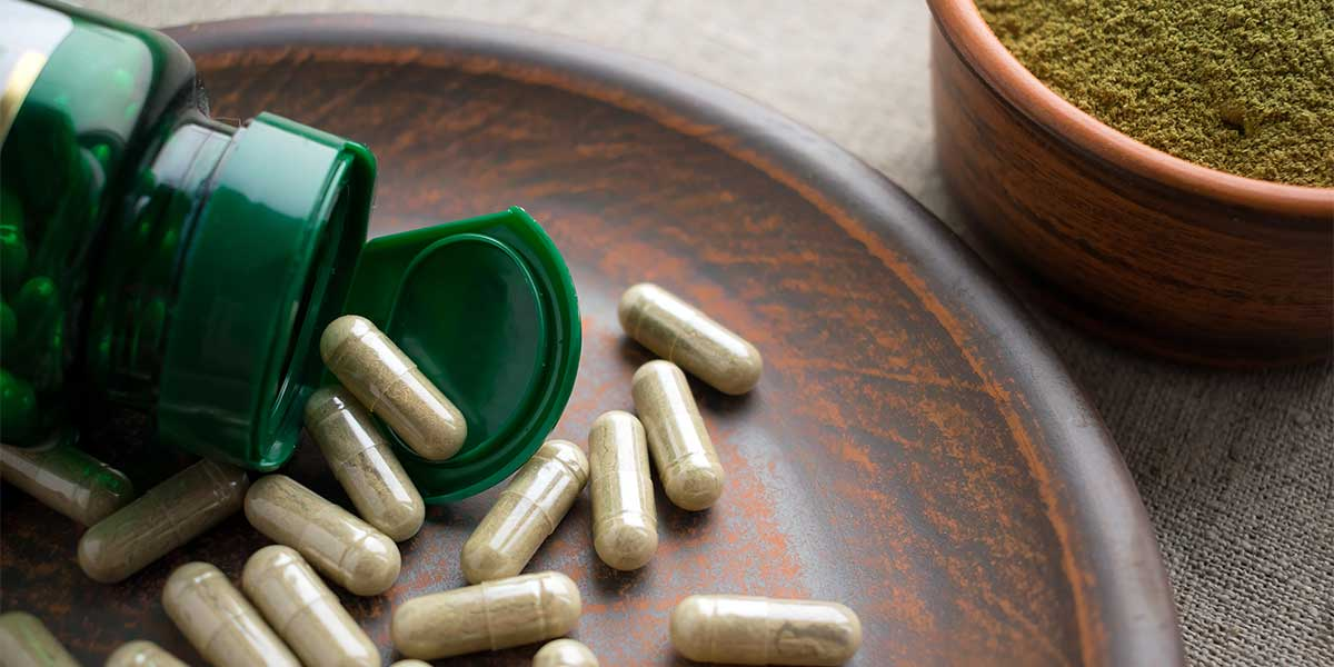 Green Tea Extracts, Close up Green capsules, bottle and powder on a clay brown plate on a burlap background.