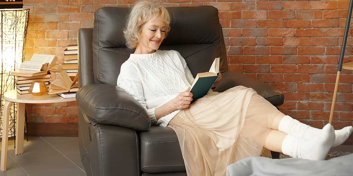 Happy senior woman sitting in armchair and reading book wearing sock for swollen feet