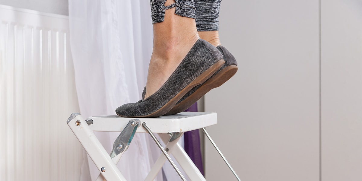 Closeup of senior woman's feet and legs standing on step stool for elderly