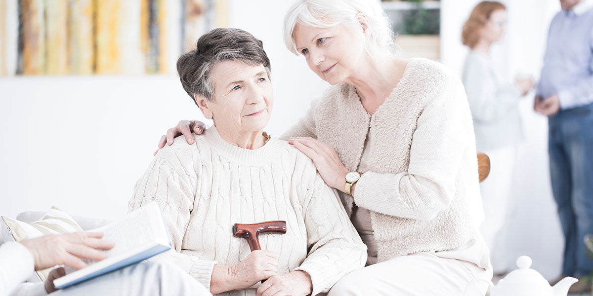 A senior sitting and comforting her friend looking ahead and holding a walking cane