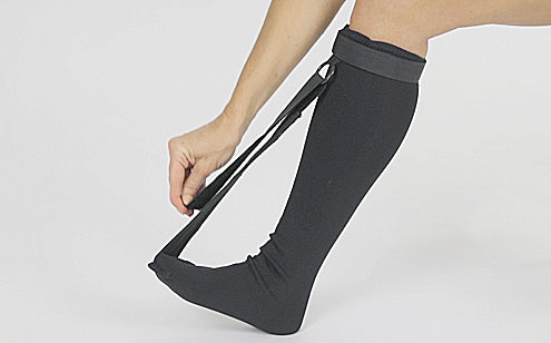 woman adjusting strap on long black stretch sock