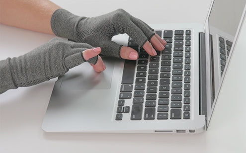 Hand wearing arthritis gloves with grips while using computer