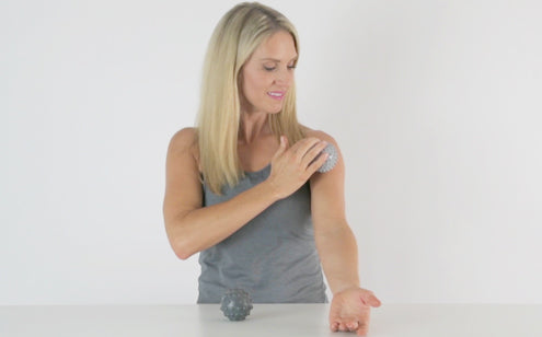 Middle age woman using massage ball in her shoulder