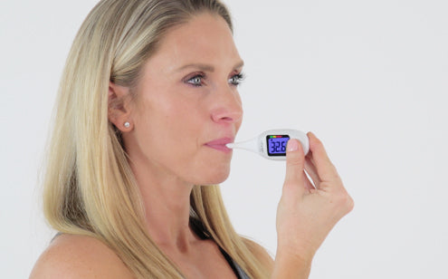 Middle age woman using oral thermometer