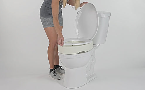 woman adjusting toilet seat riser