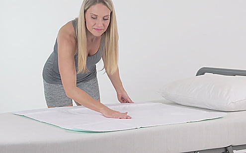 Middle age woman placing reusable incontinence pad in a bed