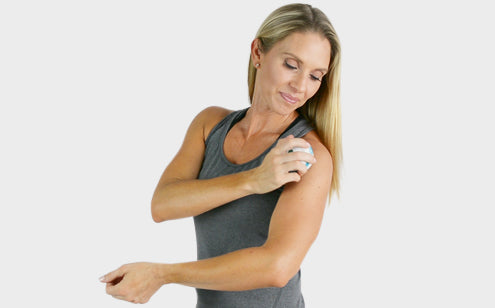 Middle age woman using a massage roller ball to reduce shoulder pain