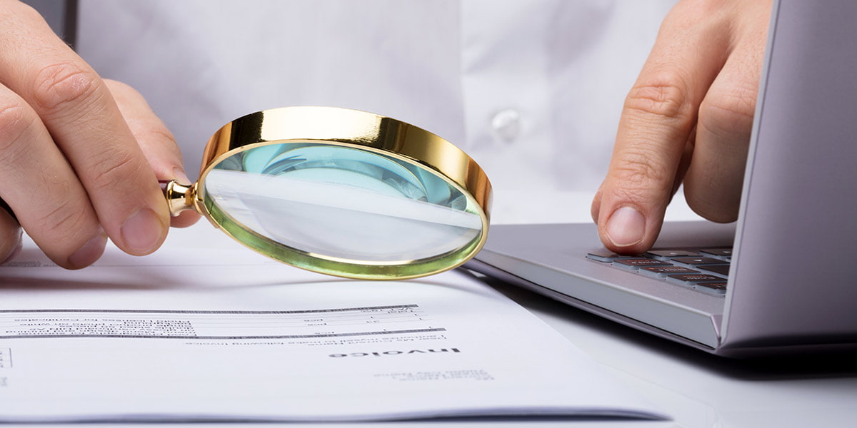 Close-up Of A Businessman Examining Invoice With Magnifying Glass