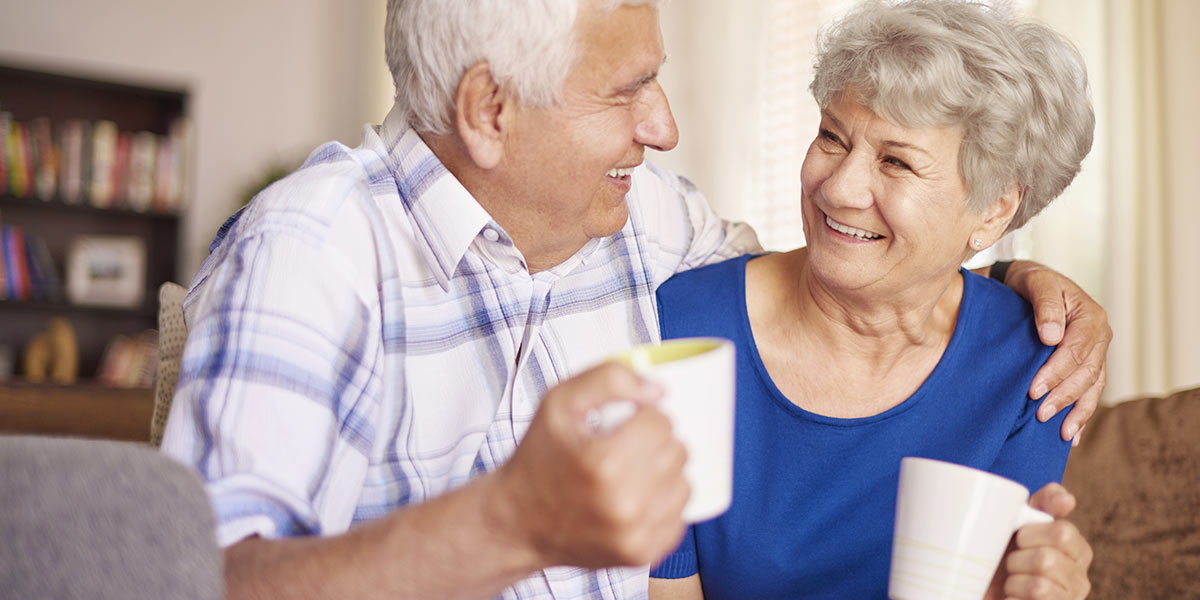 Senior couple smiling together with hot coffee
