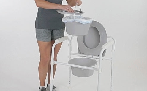 woman removing pail from folding commode
