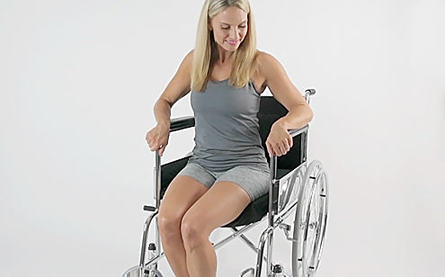 Middle age woman sitting in a wheel chair with cushion