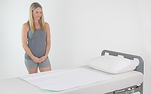 Middle age woman standing beside a bed with reusable incontinence pad