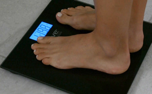 Stepping in digital bathroom scale showing accurate results