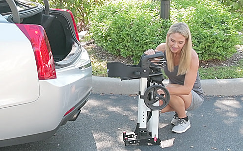 woman folding rollator to put into trunk of car