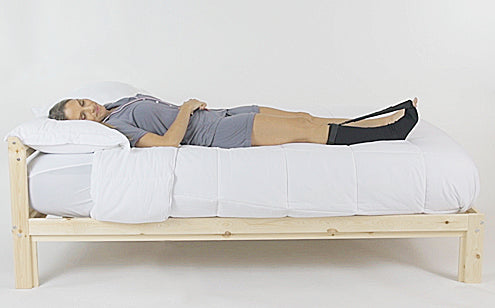 middle aged woman sleeping in bed while wearing stretch sock