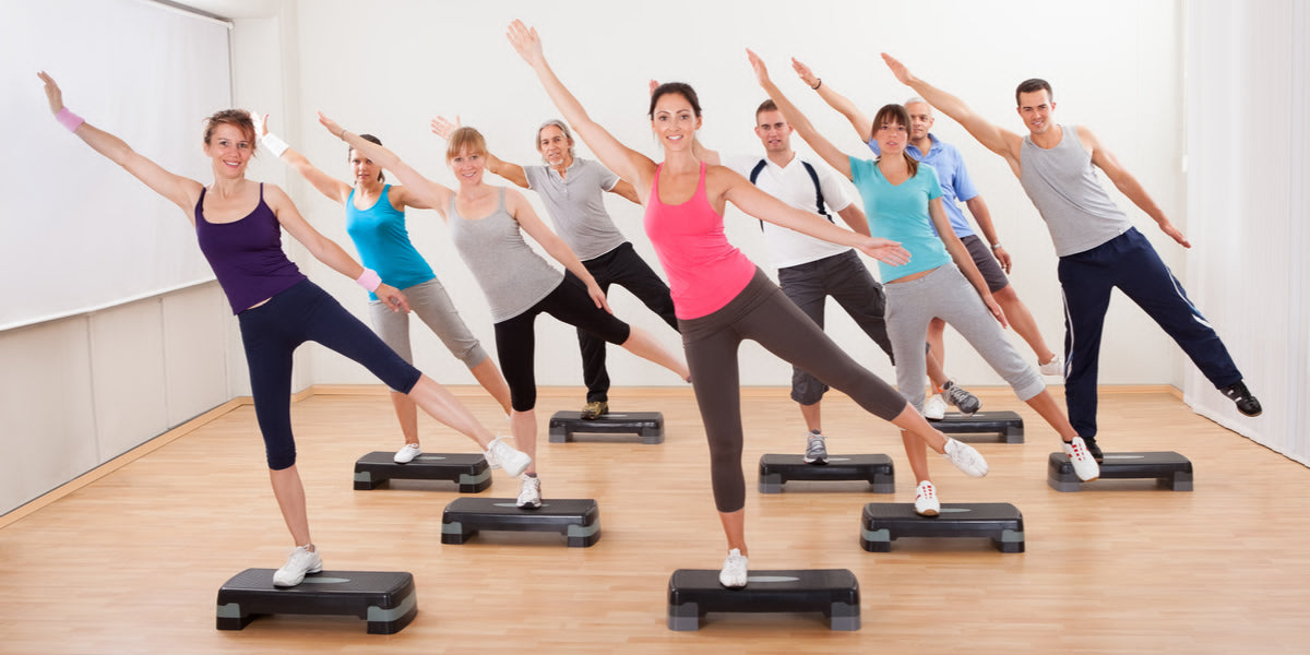 Group of people in a class doing aerobics balancing