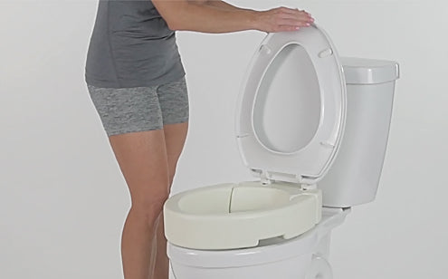 woman lifting lid of toilet seat riser