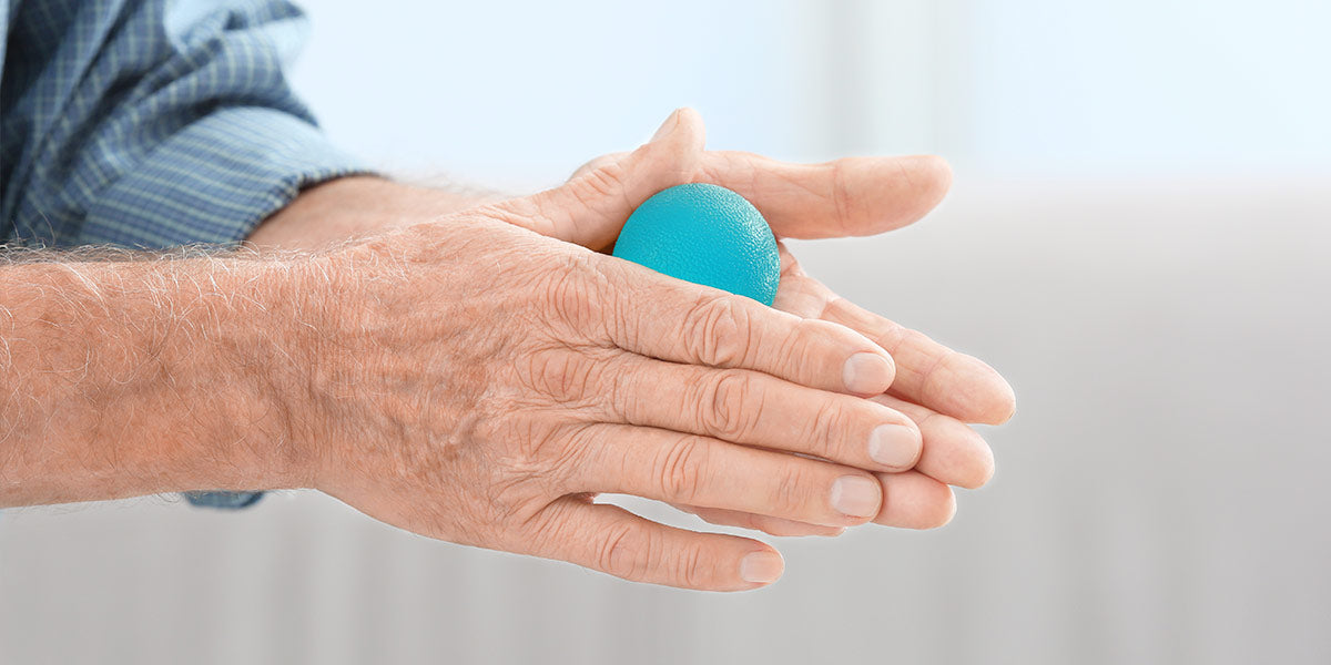 Hands of senior man doing exercise with rubber ball