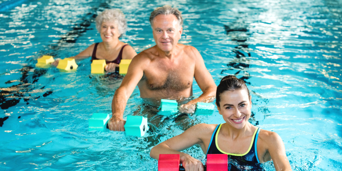 Happy active fitness mature man and senior woman doing exercise with aqua dumbbell
