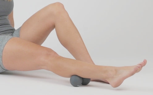 Massaging lower leg with peanut massage ball