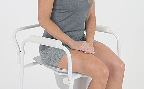 woman sitting on top of commode seat