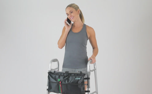 Middle age woman using phone holding walker