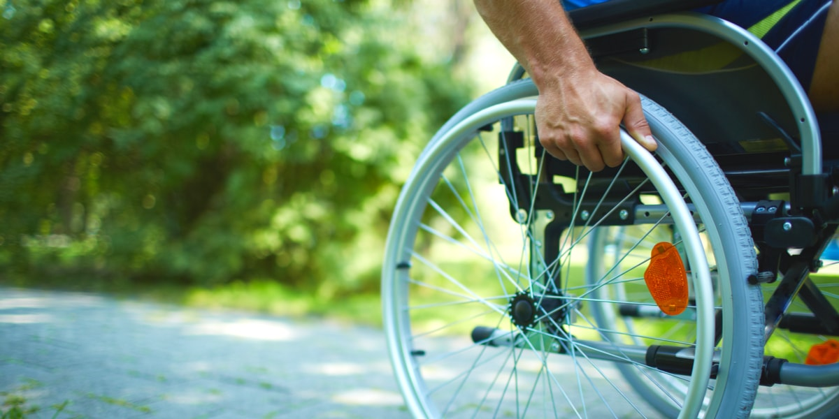 Male hand on wheel of wheelchair during walk